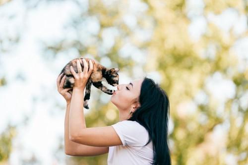 子猫を抱き上げる女性