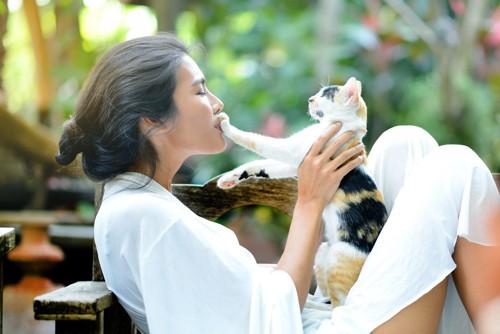 女性の口に手を伸ばす三毛猫
