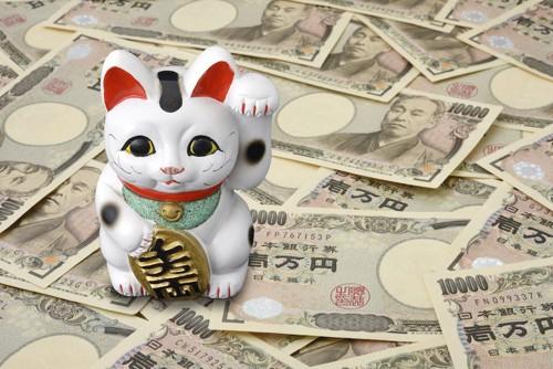 お金の上に置かれた招き猫