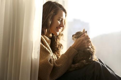窓際で猫に笑顔を向ける女性