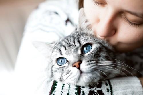 猫を抱きしめてキスをしている女性