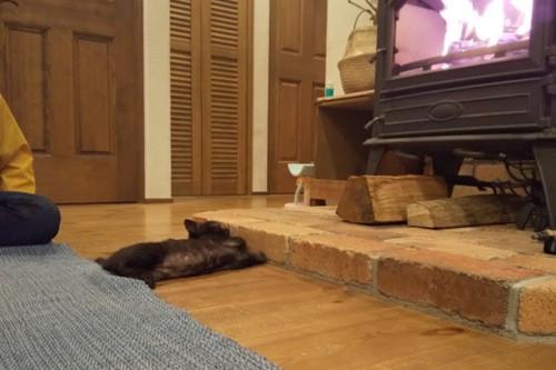 薪ストーブの前でのびる黒猫