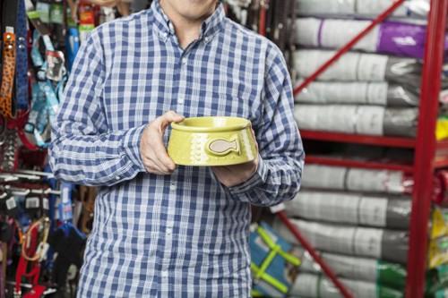ペットショップで黄色い食器を手に取る男性