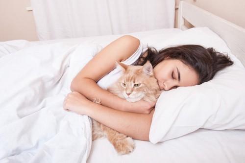 ベッドで猫を抱きしめて眠る女性