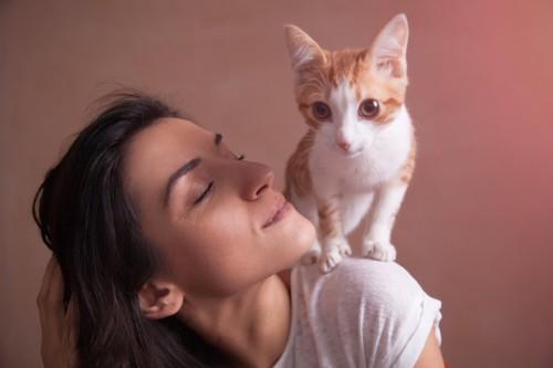 女性の肩に乗る猫