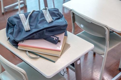 机の上のスクールバッグからはみ出したノートやペンケース
