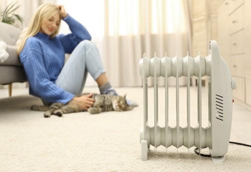 暖房器具と猫と女性