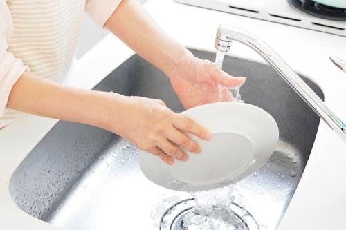 お皿を水洗いする人の手