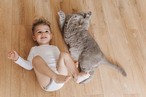同じ格好で床の上に寝転ぶ猫と子供