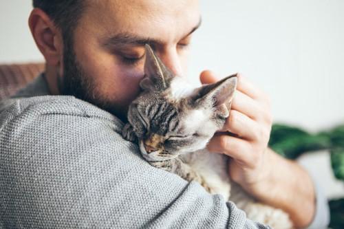 目を閉じて男性に抱きしめられている猫