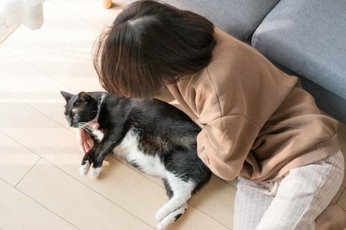 飼い主と一緒に床に寝転ぶ猫