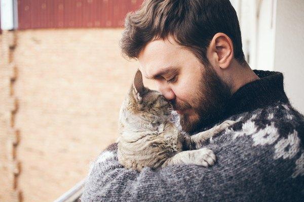 髭の男性が猫を抱っこする