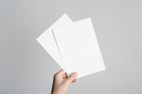 白い紙を持つ人の手