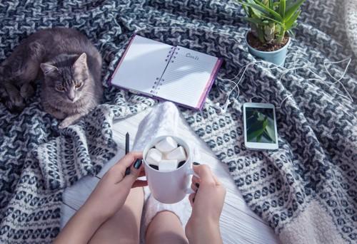 ノートを広げてくつろぐ女性と猫