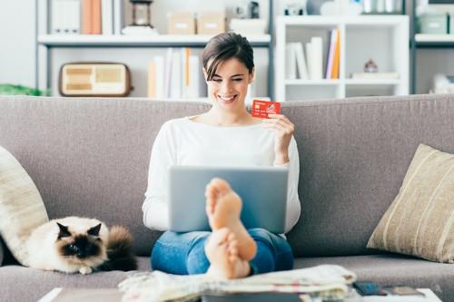 ネットで買物をする女性と隣で寛ぐ猫
