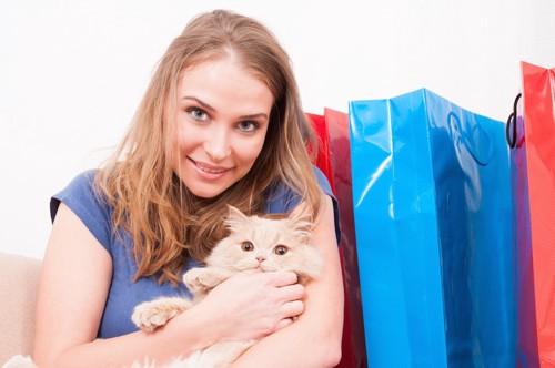 ルートートのシャッピングバッグと猫を抱いた女性