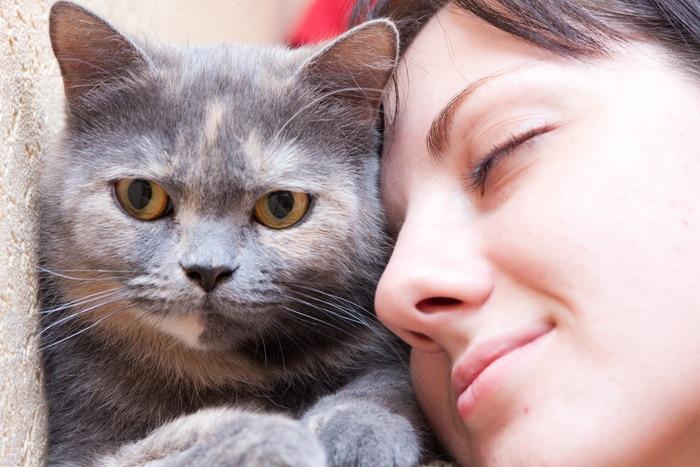 猫に顔をよせる女性