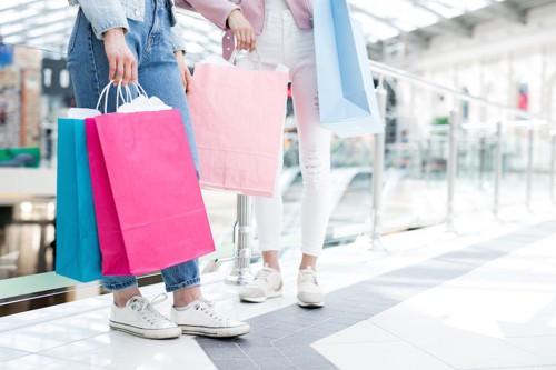 ショッピングセンターで紙袋を持って立つ2人の女性