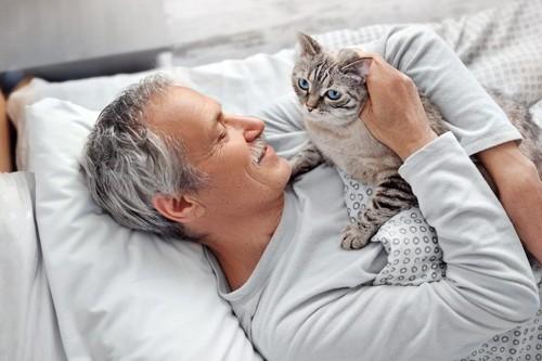 寝ている男性の上の乗っかる猫
