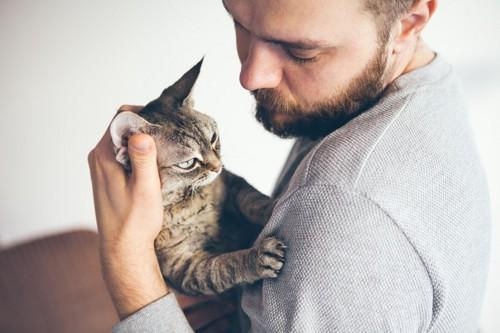 男性に抱かれて不機嫌な猫