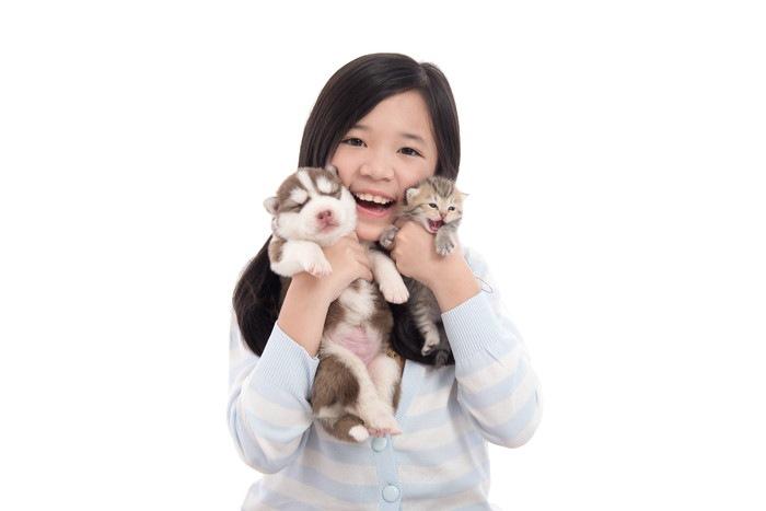 猫と犬をかかえる女の子