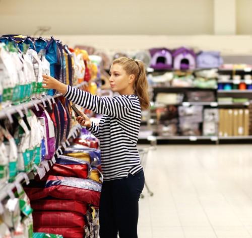 お店でペットフードを選ぶ女性