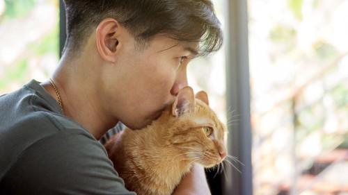 猫の後頭部に顔を寄せる男性