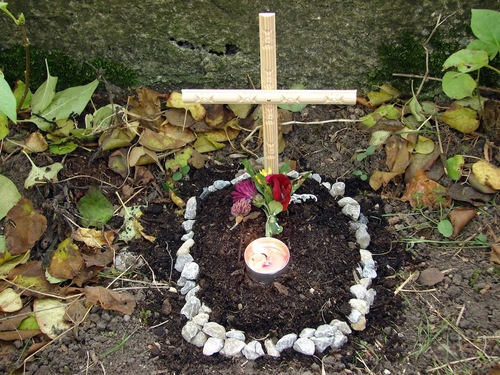 十字架を立てて小石で囲んだペットのお墓