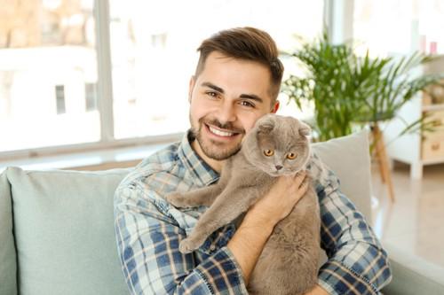 男性に抱っこされて警戒中の猫