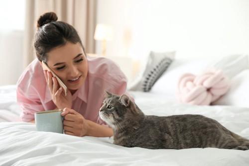 電話をしながら猫と同じ体勢になっている女性