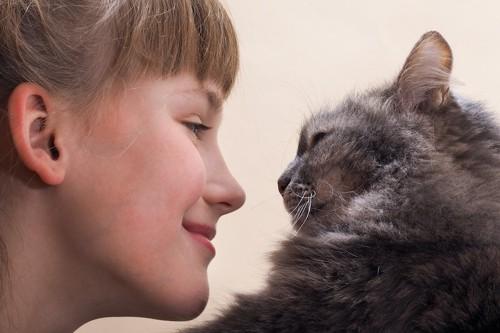 猫と見つめ合う笑顔の女性