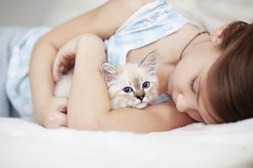 大事そうに子猫を抱いて眠る少女