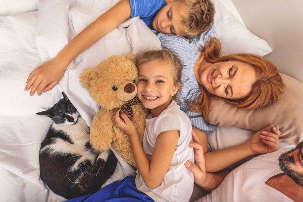 布団の上にいる家族と黒白猫