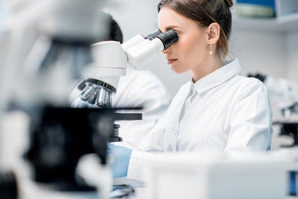 顕微鏡にて検査している女性