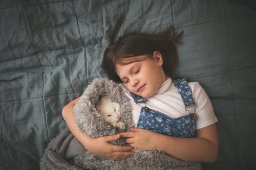 女の子に寄り添って眠る猫