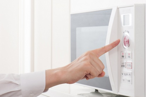 電子レンジのスイッチを押す指