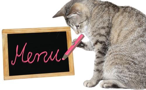 メニューボードに書いている猫