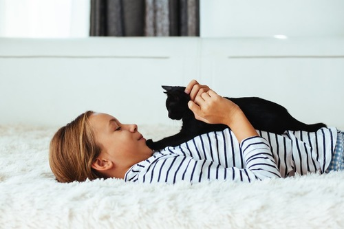 仰向けで眠る女性の上に乗って甘える黒猫