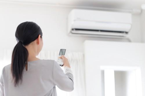 エアコンの操作をする女性