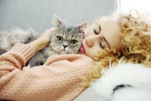 眠っている飼い主の上に乗っている猫