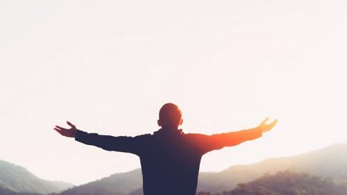 空に向かって手を広げる男性