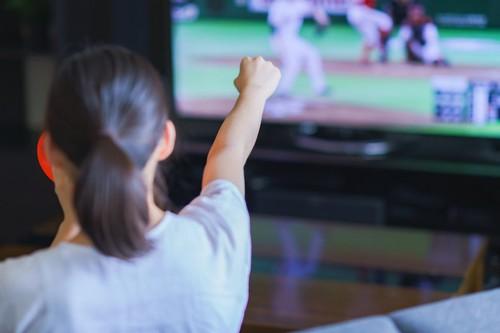 テレビで野球を見て応援している女性