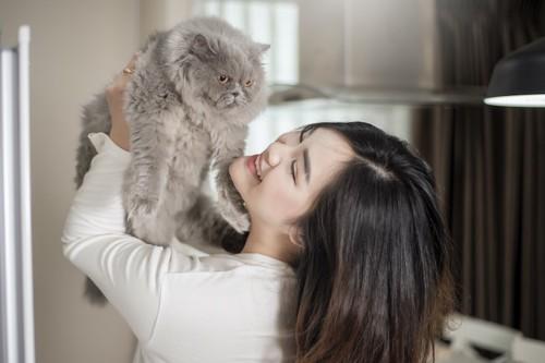 女性に抱き上げられて嫌そうな猫