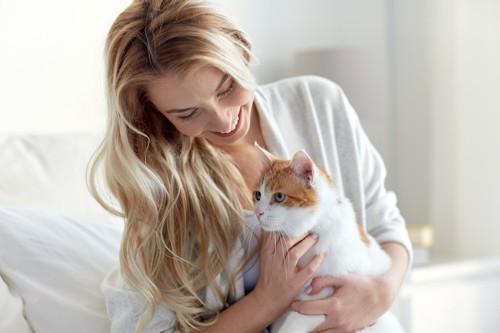 猫を抱きしめる笑顔の女性