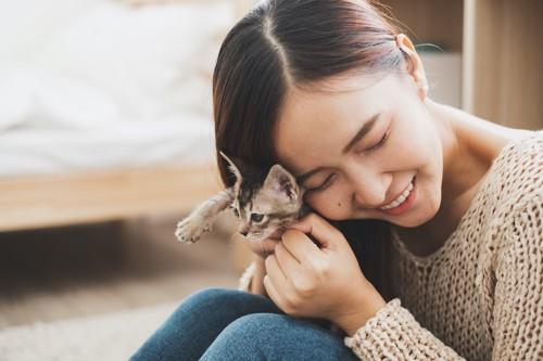 子猫を膝に乗せて顔を寄せる女性