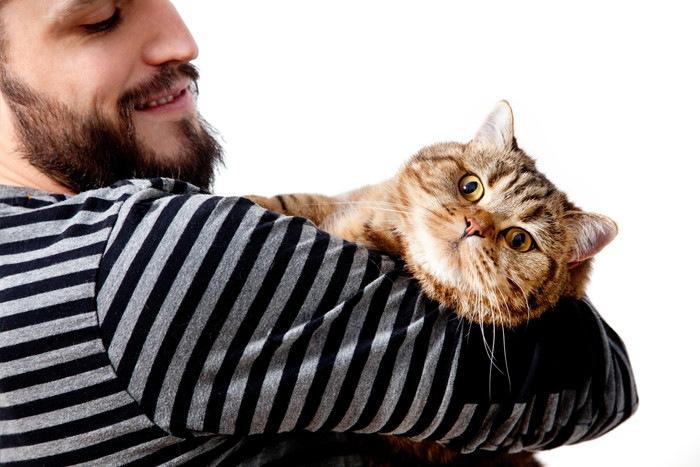 猫を抱く男性の写真