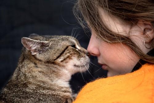 顔を寄せている女性と猫