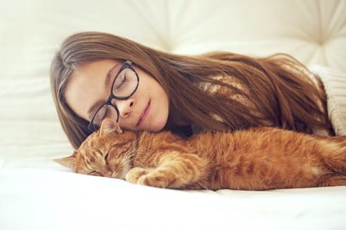 眠っている猫に添い寝する眼鏡をかけた女性