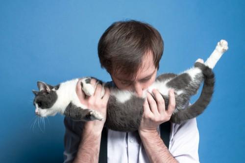猫のお腹に顔をつける男性