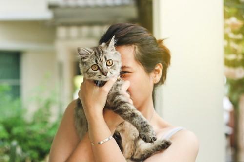猫を顔の前に抱き上げる女性